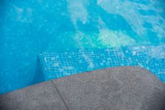 Black granite stone pool edge. Focus on corner black granite stone pool edge with see through underwater floor tiles background used for display or montage Royalty Free Stock Photo