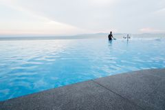 Black granite stone pool edge. Focus on black granite stone pool edge with people in swimming pool background used for display or montage object Stock Images