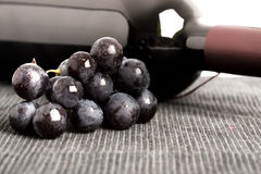 Black grapes and a bottle of red wine. Bunch of fresh black grapes and an unlabeled bottle of red wine lying on its side on a grey textile with copyspace Royalty Free Stock Image