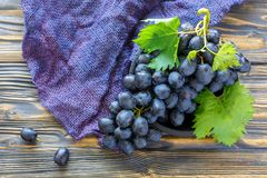 Bunch of black grapes in an old wooden bowl. Stock Photos