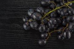 Fresh raw black grape on black wood stock images