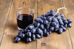 Black grapes and glass of wine on wooden background. Horizontal photo Stock Image