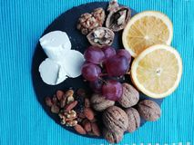 Black grapes and other fruits. Black grapes, walnuts, almonds, raisins sultanas, cranberry, orange, and goat cheese royalty free stock photography