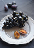 Black grapes and plums on a plate Royalty Free Stock Image