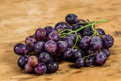 Black grapes on a rustic wooden table Royalty Free Stock Photo
