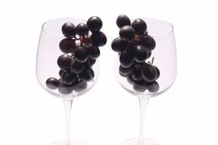 Black grapes into wine glasses Stock Photos