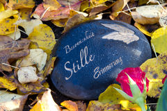 Black grave stone in autumn with german words Royalty Free Stock Photography