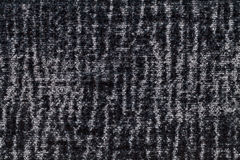 Black and gray fluffy background of soft, fleecy cloth. Texture of plush furry textile, closeup. Stock Image