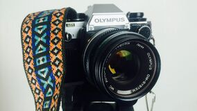 Black and Gray Olympus Dslr Camera White Orange Blue and White Strap Royalty Free Stock Photography