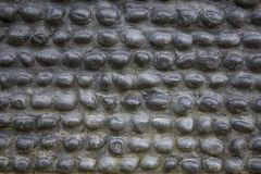 Black gray wall of oval cobble stones masonry. rough surface of the wall. stone pebble texture. A black gray wall of oval cobble stones masonry. rough surface of royalty free stock photo