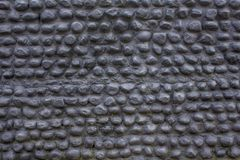 A black gray wall of oval cobble stones. rough surface of the wall. stone pebble texture. Black gray wall of oval cobble stones. rough surface of the wall. stone royalty free stock images