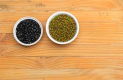 Black and green beans in bowl closeup on wood floor background.  Royalty Free Stock Photo