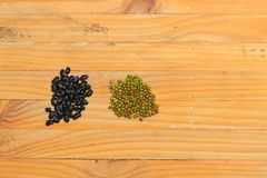 Black and green beans closeup on wood floor background. N royalty free stock photography