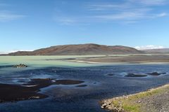 Black and green contrasting water at remote Hálslón lake in Iceland with small black sand banks royalty free stock photo