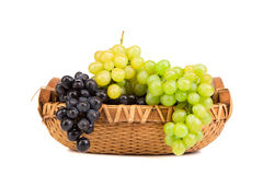 Black and green grapes in basket. Royalty Free Stock Photography
