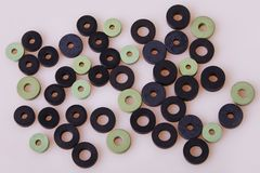 Black and green hydraulic and pneumatic o-ring seals of different sizes scattered a white background. stock image
