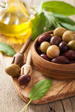 Black and green marinated olives oil sage leaf Stock Photo