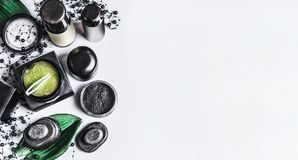 Black and green natural cosmetic products with charcoal powder and green eye patches. Charcoal cosmetic set. Facial skin care . Beauty blog promotion. Cosmetic stock photography