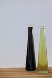 Black and green olive oil in bottle on wooden table Stock Photos