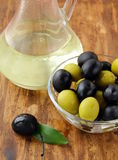 Black and green olives and a bottle of olive oil. On brown board Royalty Free Stock Photos