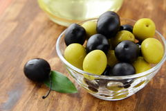 Black and green olives and a bottle of olive oil. On brown board Stock Images