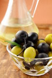 Black and green olives and a bottle of olive oil. On brown board Royalty Free Stock Photo