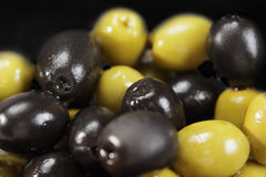 Black and green olives in a bulk. Closeup photo selective focus royalty free stock photo