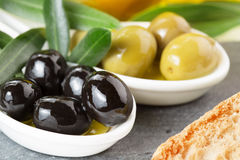 Black and green olives. Crouton and olive leaves royalty free stock photography