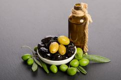 Black and green olives mixed in the porcelain bowl and Virgin olive oil. Black and green  olives  mixed in the  porcelain bowl and Virgin olive oil in a glass Royalty Free Stock Images