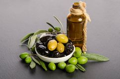 Black and green olives mixed in the porcelain bowl and Virgin olive oil. Black and green  olives  mixed in the  porcelain bowl and Virgin olive oil in a glass Royalty Free Stock Photography