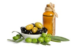 Black and green olives mixed in the porcelain bowl and Virgin olive oil. In a crystal bottle on white background stock image