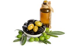 Black and green olives mixed in the porcelain bowl and Virgin olive oil. In a crystal bottle on white background Stock Photos