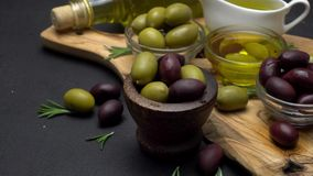 Black and green olives and oil on wooden cutting board stock video