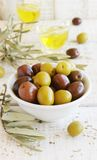 Black and green olives, olive oil on a white Stock Photography