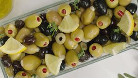 Black and green olives in a plate. Decorated with lemon, red pepper, mint leaves. Breakfast concept. Products is on white
