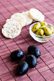 Black and green olives with rice cakes on bamboo napkin Stock Photography