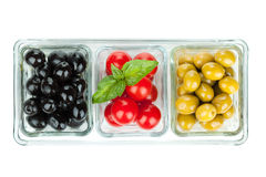 Black and green olives and tomatoes with basil Stock Photo