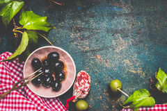 Black and green olives on traditional red plaid napkin on dark rustic background, top view, place for text. Stock Images