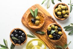 Black and green olives on white. Black and green olives in wooden bowls and olive oil bottle on white background. Top view copy space Stock Photos