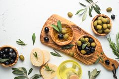 Black and green olives on white. Black and green olives in wooden bowls, olive oil bottle and bread. Top view on white background Royalty Free Stock Images