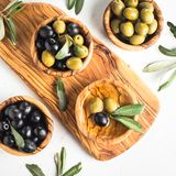 Black and green olives on white. Black and green olives in wooden bowls and olive oil bottle. Top view on white background Royalty Free Stock Photos