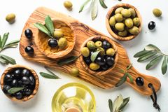 Black and green olives on white. Black and green olives in wooden bowls and olive oil bottle. Top view on white background Stock Photos