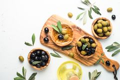 Black and green olives on white. Black and green olives in wooden bowls and olive oil bottle. Top view on white background Royalty Free Stock Photography