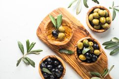 Black and green olives on white. Black and green olives in wooden bowls and olive oil bottle. Top view on white background with space for text Stock Photography