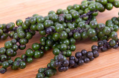 Black and green peppercorn. On wood table stock photo