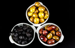 Black, green, and pink olives in bowls. Stock Photo