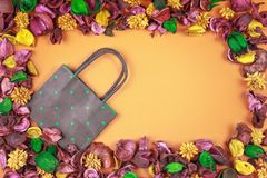 Black and green polka dot paper shopping bag surrounded by colorful dried flowers and leaves frame. Royalty Free Stock Photography