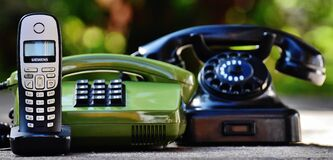 Black and Green Rotary Telephones Beside Cordless Home Telephone Stock Photo