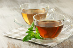 Black and green tea. Cups of black and green tea with mint on rustic table Stock Photo