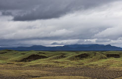 Black Green Volcanic Landscape Iceland. Volcanic landscape on Iceland with grass, lava, mountains and black sand and dark rain clouds in the sky Royalty Free Stock Photo